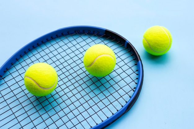 Raqueta de tenis con pelotas sobre superficie azul