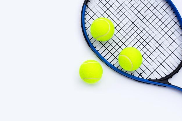 Raqueta de tenis con pelotas sobre superficie blanca