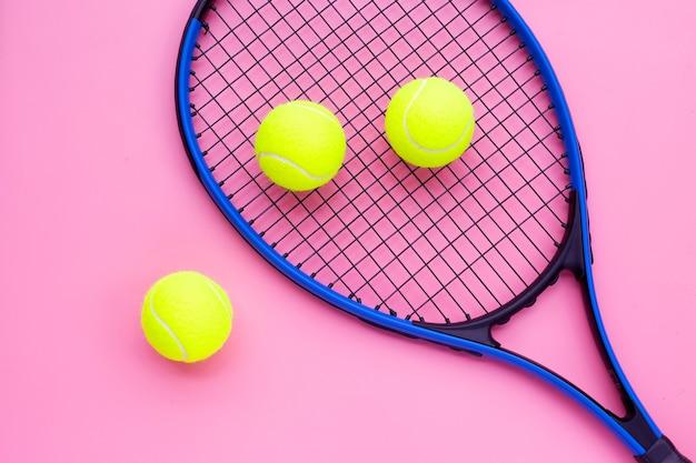Raqueta de tenis con pelotas en superficie rosa