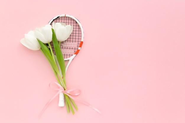 Raqueta de tenis y tulipanes blancos sobre fondo rosa con espacio de copia