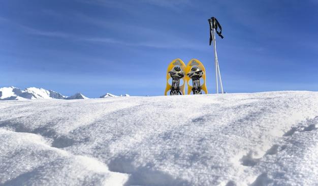 Raquetas de nieve en la nieve en la cima de la montaña bajo el cielo azul