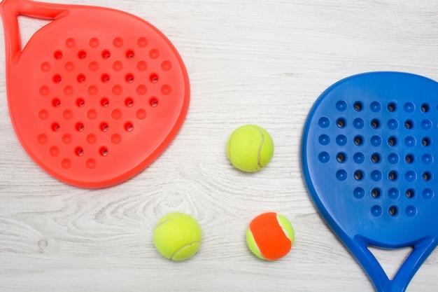 Raquetas de pádel azul y rojo y pelota sobre mesa de madera blanca vista superior