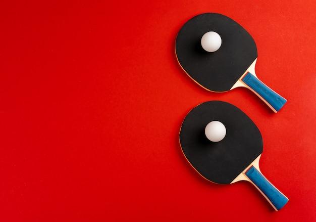 Raquetas de ping pong negro sobre fondo rojo.