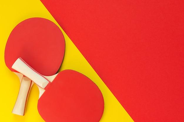 Raquetas de ping pong de tenis rojo y aislado sobre un fondo rojo y amarillo, equipamiento deportivo para tenis de mesa