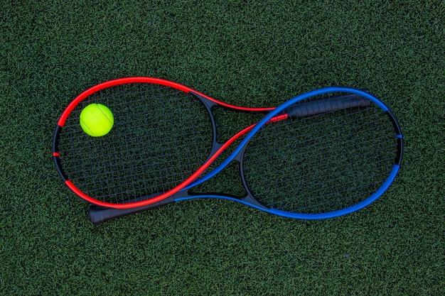Raquetas de tenis con pelota sobre fondo de hierba verde