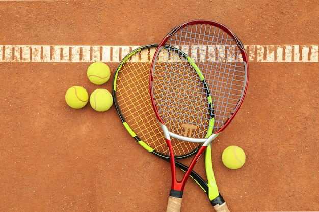 Raquetas de tenis con pelotas de tenis en tierra batida