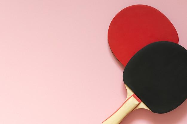 Raquetas de tenis de ping pong negras y rojas aisladas sobre un fondo rosa, equipamiento deportivo para tenis de mesa