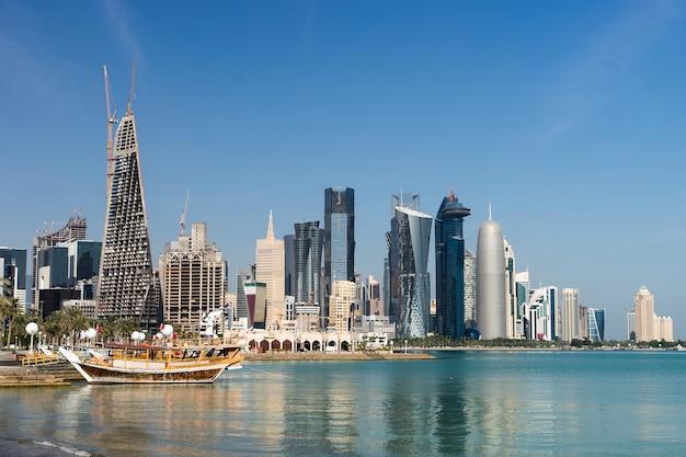 Rascacielos en el centro de la ciudad con agua y primer plano del barco de doha, qatar.