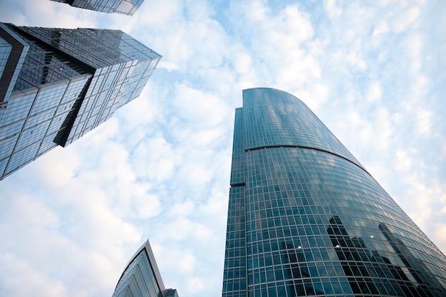 Rascacielos de oficinas y residenciales sobre fondo de cielo azul. bienes raíces comerciales. distrito de la ciudad de negocios moderno. exterior de edificios de oficinas.