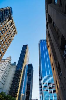 Rascacielos vidriosos de debajo del paisaje urbano al atardecer