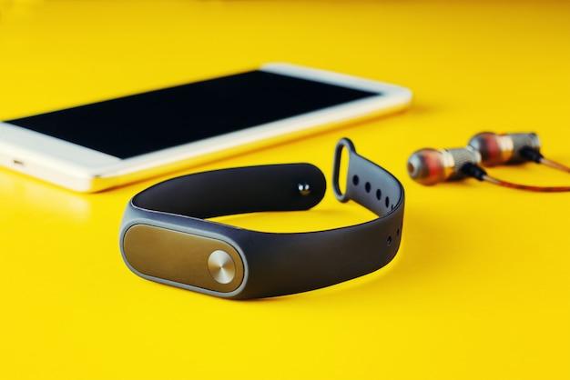 Rastreador de ejercicios, auriculares y teléfono inteligente sobre fondo amarillo