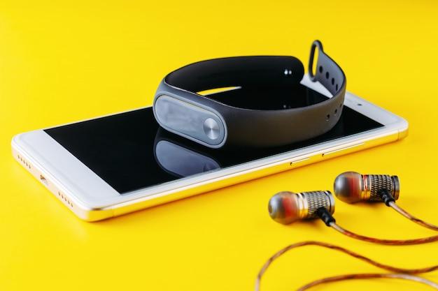 Rastreador de fitness, teléfono inteligente y auriculares sobre fondo amarillo