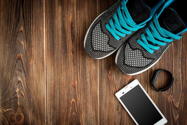 Rastreador de fitness y zapatillas en mesa de madera.