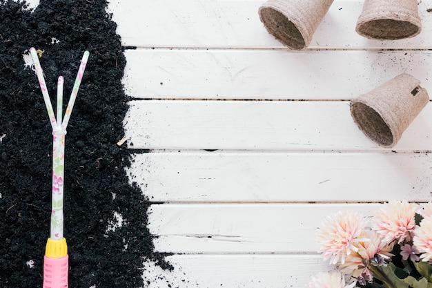 Rastrillo de jardinería en el suelo sobre la mesa de madera con maceta de turba y flores