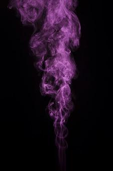 Rastro rosado del humo del remolino en fondo oscuro