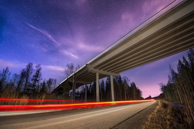 Rastros de los faros en el camino en la noche