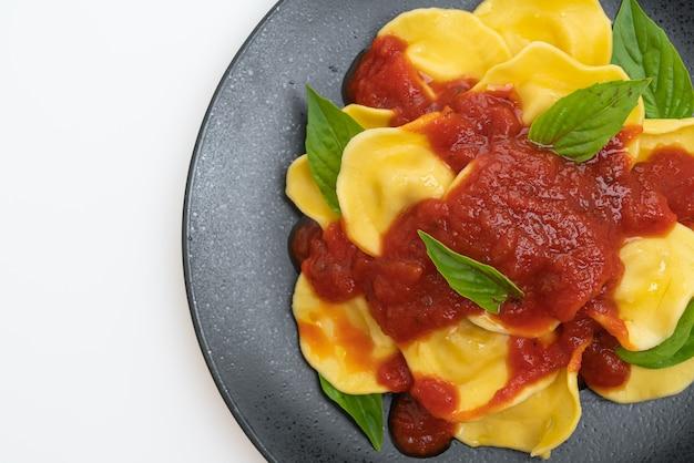 Ravioles con salsa de tomate y albahaca aislado sobre mesa blanca