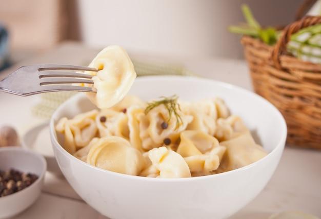 Raviolis italianos hechos en casa de las bolas de masa hervida de la carne del pelmeni en el tazón de fuente blanco.