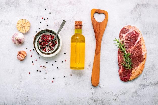 Raw striplion steak creado sobre fondo de hormigón blanco. lay flat de filete de ternera cruda fresca con romero y especias en la vista superior de fondo de hormigón en mal estado blanco.