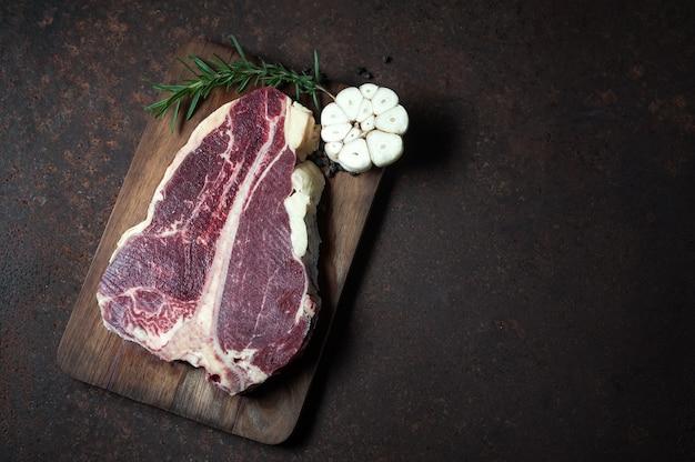 Raw t - filete de hueso en la vieja mesa de cocina rústica