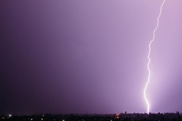 Un rayo en un cielo púrpura oscuro cae al suelo sobre la ciudad