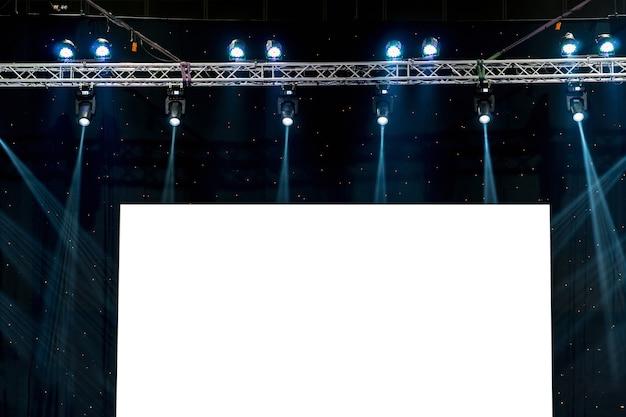 Rayos luminosos de la iluminación del concierto contra un fondo oscuro