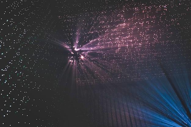 Rayos de luz a través de pequeños agujeros en un espacio de metal oscuro