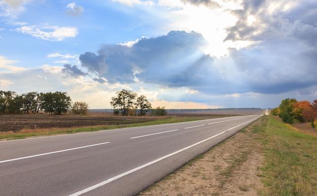 Los rayos del sol atraviesan las nubes y el camino vacío