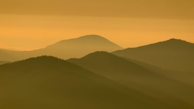 Los rayos del sol iluminan las cimas de las montañas a través de la niebla.
