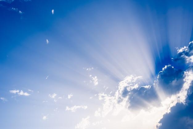 Rayos de sol que se levantan de una gran nube en el cielo azul intenso en una tarde de verano