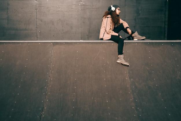 Raza mixta hipster adolescente con expresión facial grave disfrutando de la música y sentado en el skate park.