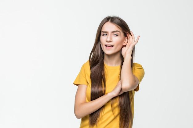 Reacción de la mujer joven sobre algo escuchado aislado sobre la pared blanca
