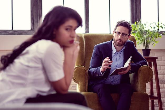 Real profesional. agradable psicólogo serio sentado en el sillón mientras le hace una pregunta a su paciente