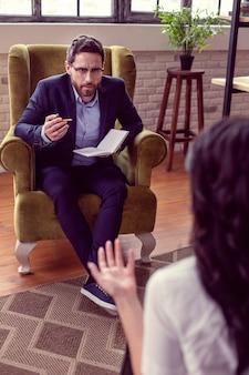 Real profesional. buen psicólogo profesional hablando con su paciente mientras está en el trabajo