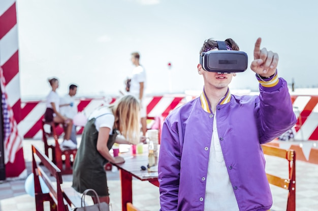 Realidad virtual. hombre joven con máscara electrónica mientras apunta a algo extraño