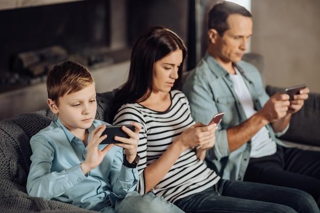 Realidades modernas. agradable familia joven sentada en el sofá y usando sus teléfonos, siendo adicta a ellos, sin notar nada alrededor.