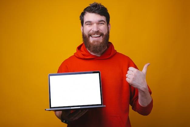 Realiza compras en línea. la foto de un hombre barbudo sostiene una computadora portátil y muestra el pulgar hacia arriba o como gesto.