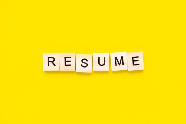 Reanudar la palabra bloques de madera con letras en la parte superior de la mesa amarilla. concepto de gestión de recursos humanos y reclutamiento y contratación