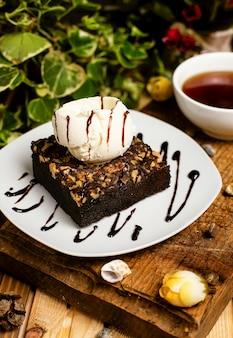 Una rebanada de brownie de chocolate con helado de nuez y vainilla.