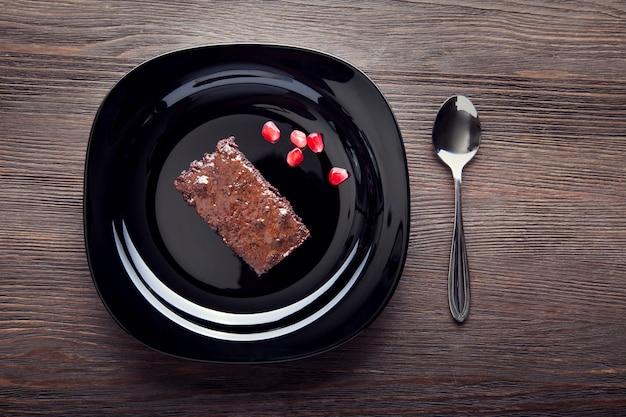 Rebanada de brownie en plato negro sobre una mesa de madera con una cuchara y semillas de granada