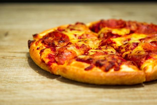 Rebanada caliente de la pizza con queso de fusión en una tabla en comida del italiano de la pizza del restaurante.