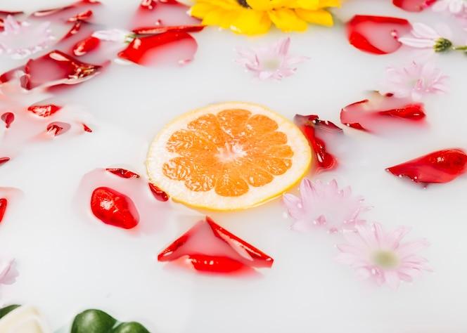 Rebanada de pomelo rodeado de flores y pétalos de leche
