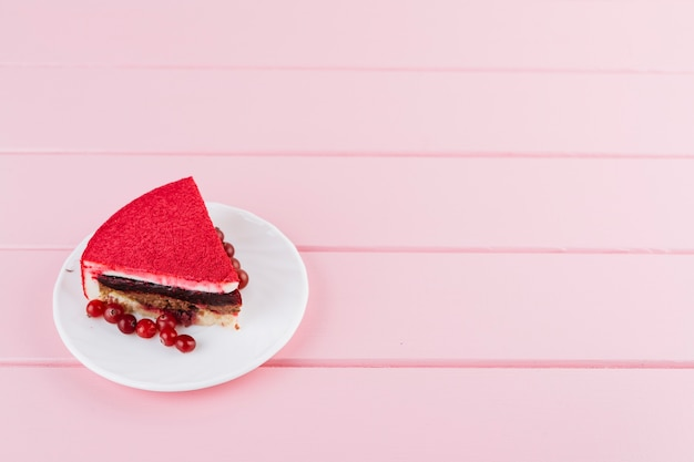 Rebanada deliciosa de la torta con las bayas de la pasa roja en la placa blanca sobre el contexto rosado del tablón