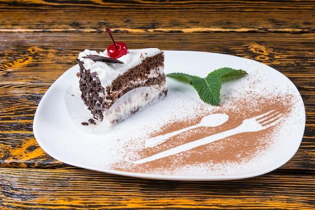 Rebanada de delicioso pastel de chocolate adornado con una cereza y menta servido en un plato con detalle decorativo de un tenedor y cuchara en chocolate en polvo