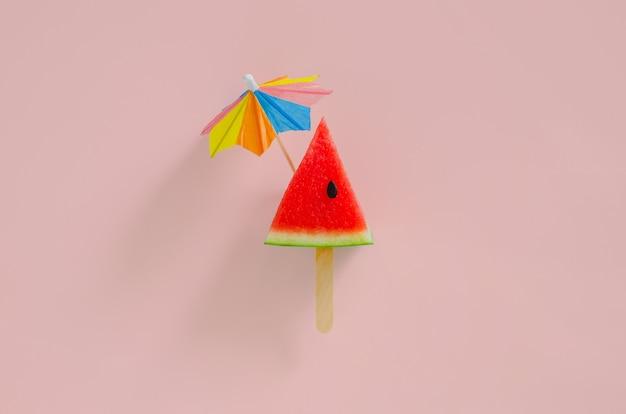 Rebanada de diseño de sandía como helado con palo que tiene un paraguas de cóctel en la parte superior