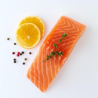 Rebanada de filete de salmón crudo crudo fresco sobre una superficie blanca con condimentos y limón, vista superior