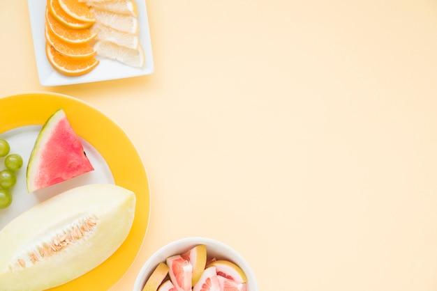 Rebanada de frutas cítricas; sandía y melón sobre fondo beige