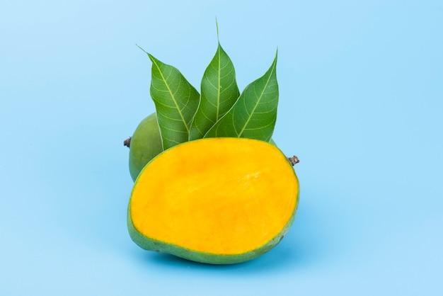 Rebanada de mango amarillo con hoja aislada en azul