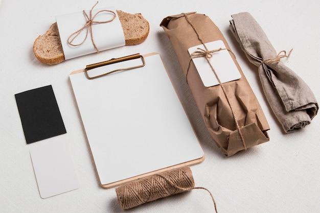Rebanada de pan y baguette envuelto en ángulo alto con bloc de notas en blanco y etiquetas