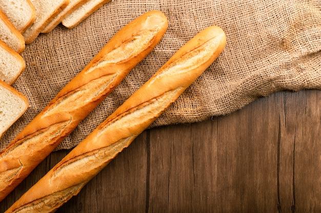 Rebanada de pan con baguette sobre mantel